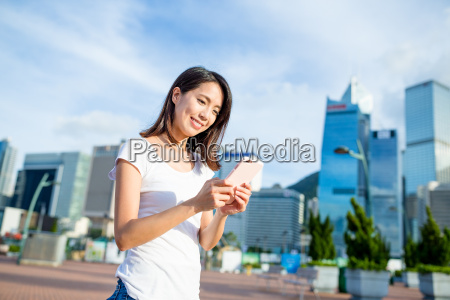 woman using cellphone at city of