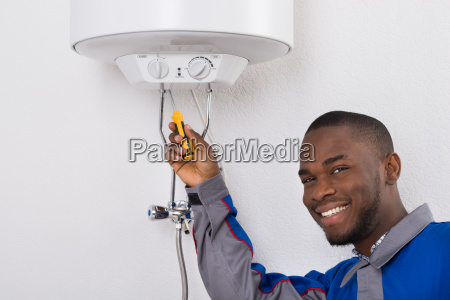 worker fixing electric boiler with screwdriver
