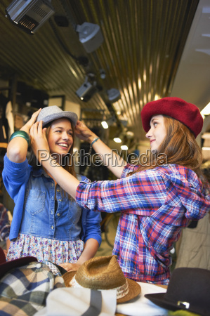 young friends trying on hats in