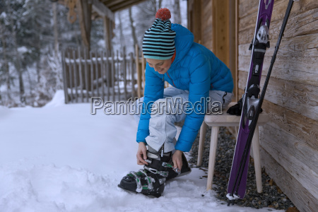 woman adjusting ski boots in snow