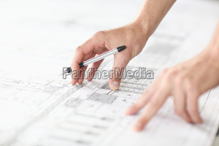 young architect studying blueprints
