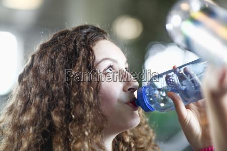 teenage girl drinking from water bottle