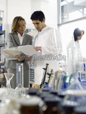 businesswoman talking to scientist in laboratory