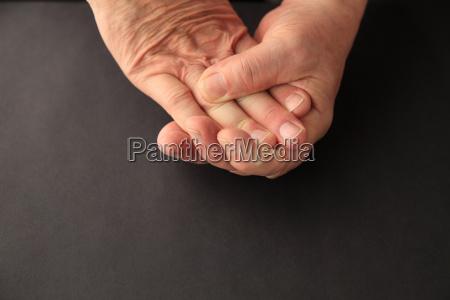 older man grips his numb fingers