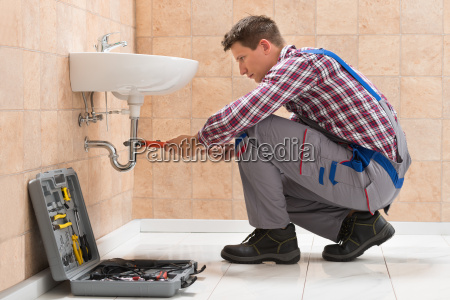 young male plumber fitting sink