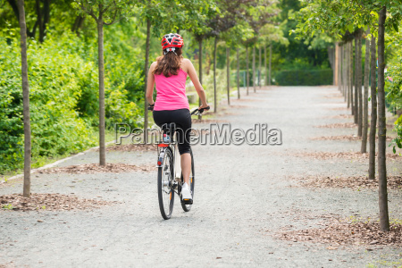 female cyclist riding away on bicycle