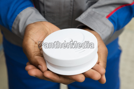 electrician holding smoke detector