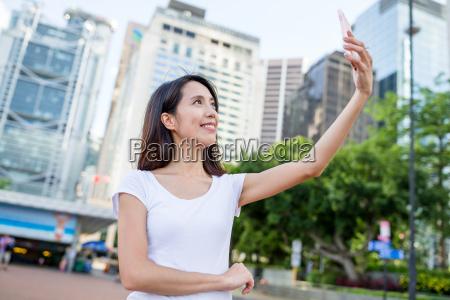 woman taking photo on street