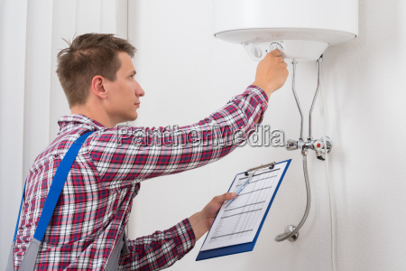 male plumber adjusting temperature of electric