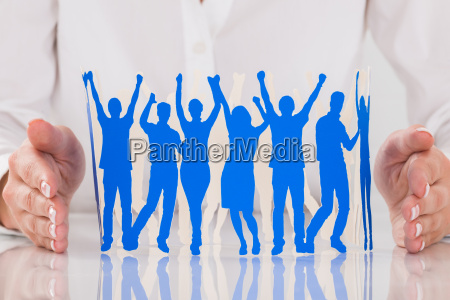persons hand protecting paper cut out