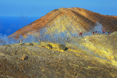 people walking through fumaroles on volcano