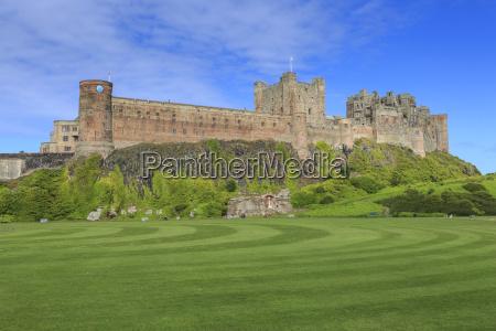 bamburgh castle under a blue summer