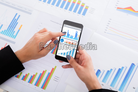 businesswoman analyzing financial graphs using smartphone