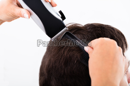 hairdresser cutting mans hair with electric