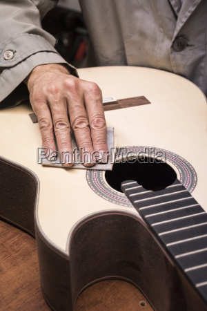 luthier manufacturing a guitar close up