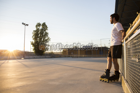 man with rollerblades leaning on a
