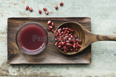 glass of pomegranate juice and wooden