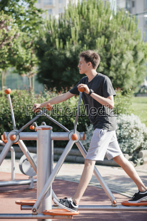 teenager exercising on outdoor fitness equipment