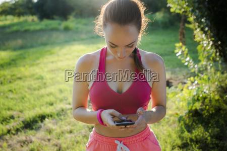 italy tuscany sportswoman using smartphone