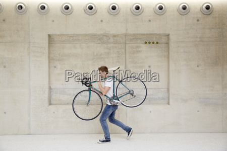 young man carrying bicycle on his