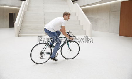 young man riding bicycle in a