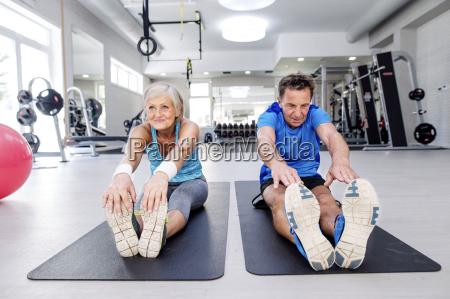 senior man and mature woman exercising