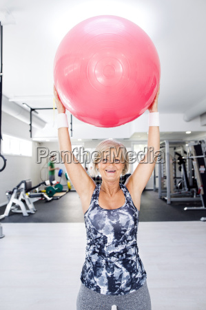 smiling mature woman lifting up fitness