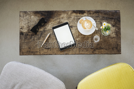 digital tablet sunglasses and cup of