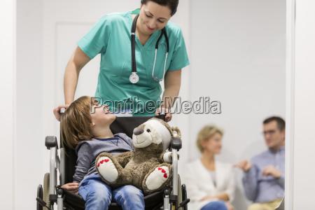 nurse pushing boy in wheelchair on
