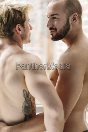 gay couple embracing at window