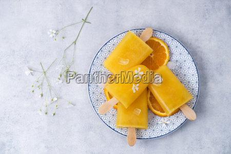 dish with homemade orange popsicles