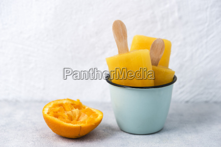 enamel cup of homemade orange popsicles