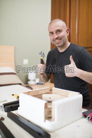 man assembling furniture at home thumbs