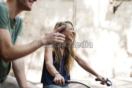 laughing woman with bicycles beside her