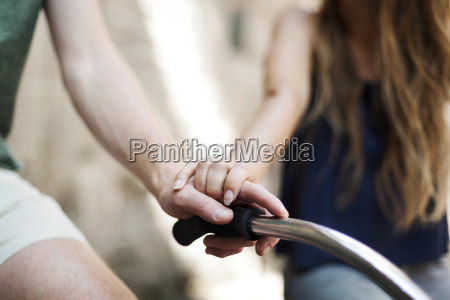hands of couple on handlebar of