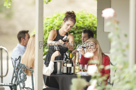 waitress and clients in restaurant examining