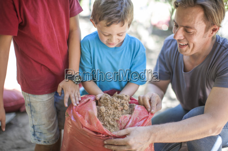 father and sons with sack of