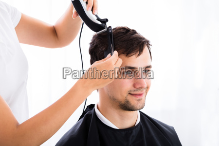 man getting his haircut from hairdresser
