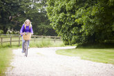 teenage girl riding bike along country
