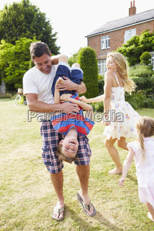 family having fun playing in garden