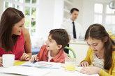 mum helps children with homework as