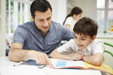 father helping son with homework using
