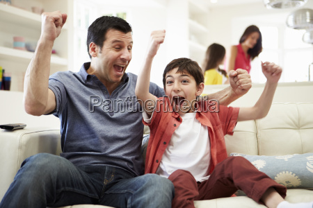 father and son watching sports on