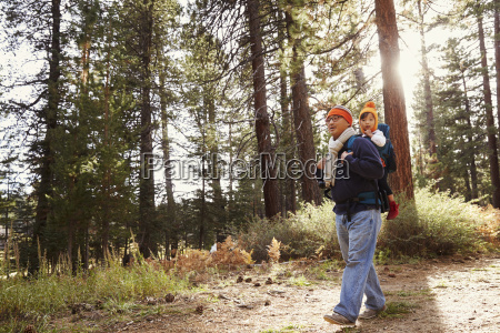 dad walking in forest with toddler