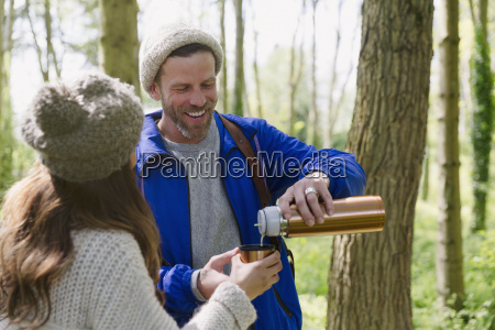 couple hiking and drinking coffee from
