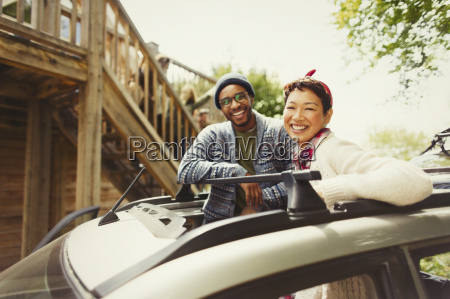 portrait smiling couple standing in car