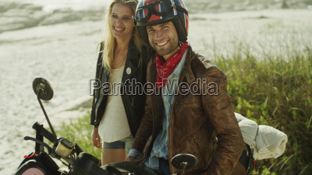 portrait smiling young couple at motorcycle