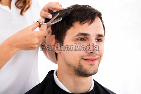 man getting haircut from hairdresser