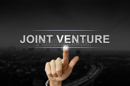 business hand pushing joint venture button