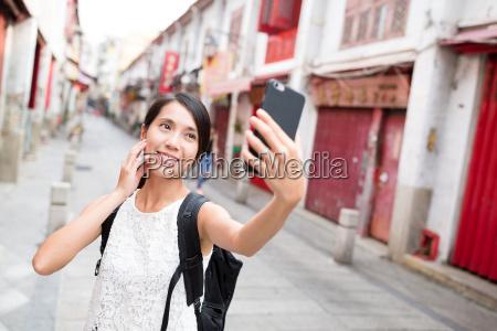 woman taking selfie by camera in